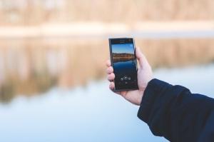 man-hand-smartphone-lake